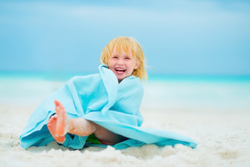 Portrait of laughing baby girl wrapped in towel sitting on beach