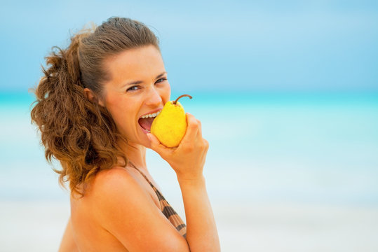 Portrait of young woman eating pear on beach