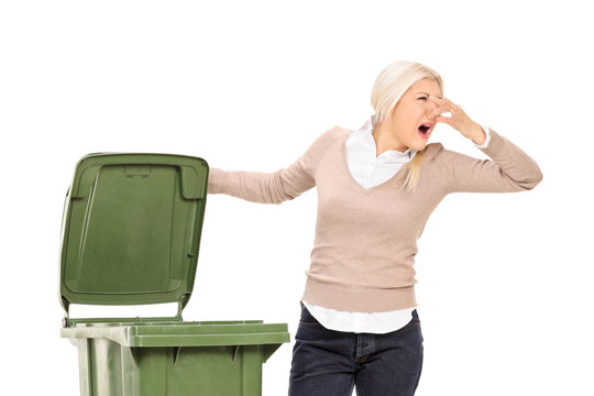 Woman opening a stinky trash can