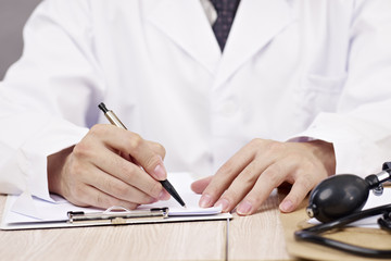 hands of doctor writing on notepad