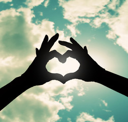 two hands making a heart shape in the sky