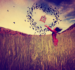 a girl in a field tossing a birdcage in the air with birds