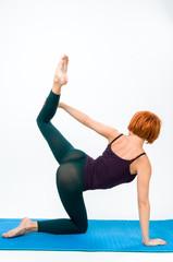 Yoga posing on a gray studio background