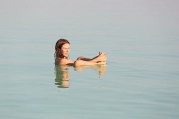 Beautiful girl floating at the turquoise water of Dead sea