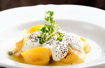 Italian ravioli tortellini with cream sauce and black truffles