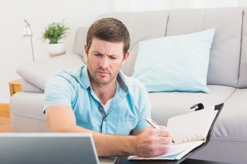 Focus man looking at is laptop and writing on a notebook