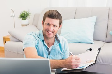 Smiling man writing on a notebook
