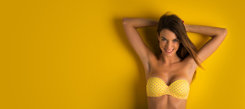 Beautiful smiling girl portrait against colorful yellow backgrou