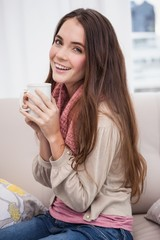 Pretty brunette having coffee on the couch