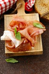 smoked ham jamon (Parma) with basil leaves