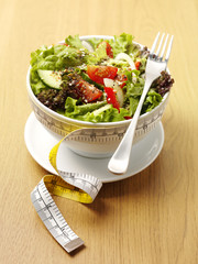 A bowl of mixed salad with a tape measure