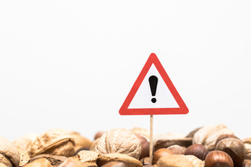 Warning Sign next to a Mixture of Nuts