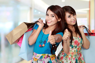 Woman with shopping bags showing thumb up