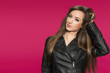 Sexy young brunette woman in leather jacket