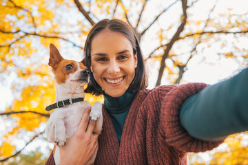 Portrait of smiling young woman with dog outdoors in autumn