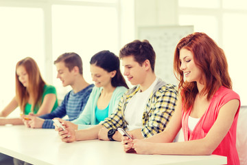 smiling students with smartphones at school