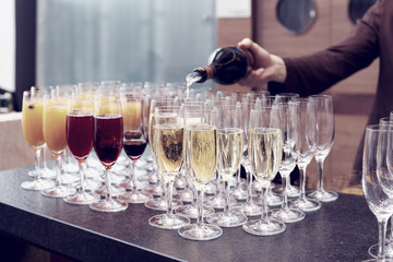 Bartender is pouring sparkling wine in glasses, toned image