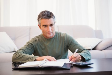 Man taking notes with calculator and notepad on the table