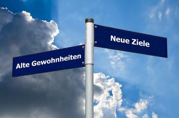 Straßenschild vor bewölktem/blauen Himmel mit Schriftzug 'Alte Gewohnheiten' vs. 'Neue Ziele'