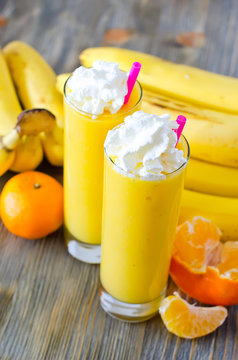 Yellow smoothie in glasses with tropical fruits and straw to dri