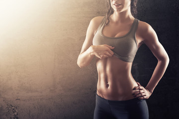 Fit young woman showing her abs
