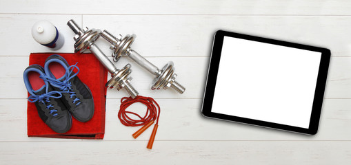 fitness equipment and blank digital tablet on gym floor
