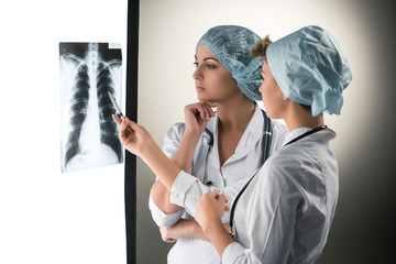 Two attractive young doctors looking at x-ray results