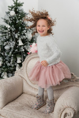 Child girl with sheep toy jump at Christmas