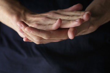 adult man clasped hands