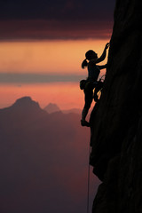 Elegant female climber ascents natural rock against sunset