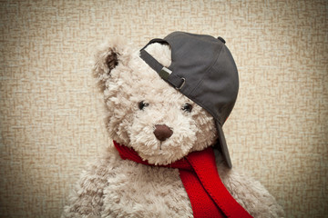 Teddy bear in a red scarf and a black baseball cap. plush toy