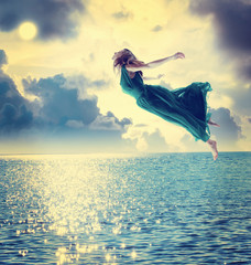 Beautiful girl jumping into the night sky