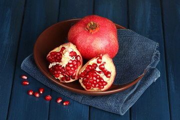 Juicy ripe pomegranates on blue wooden table