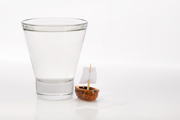 Closeup of a walnut shell boat with a sail, close to a transparent glass full of water or alcohol