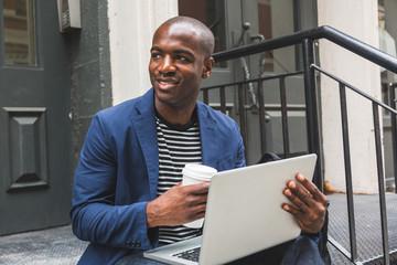 Black Guy Using Notebook in New York