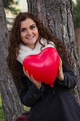 Smiling girl holding a heart made of balloons