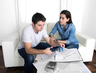 husband cutting credit card with scissors woman trying to stop