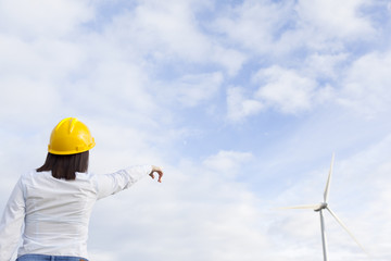 Female engineer pointing to windmills
