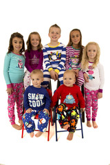 Seven beautiful young children wearing winter pajamas smiling