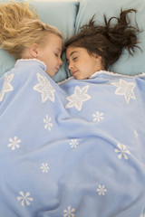 Two young girls in bed asleep under a snowflake blanket