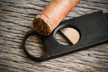Cigar and Cigar Cutter on Rustic Wood Background