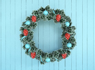 Green wreath with blue and red bow on aqua rustic wood