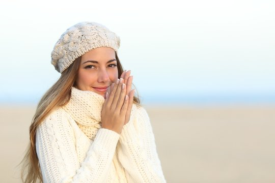 Woman warmly clothed in winter on the beach