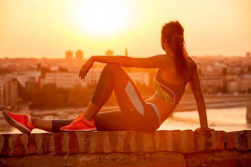 young Sports woman enjoying in the sunset after a hard workout