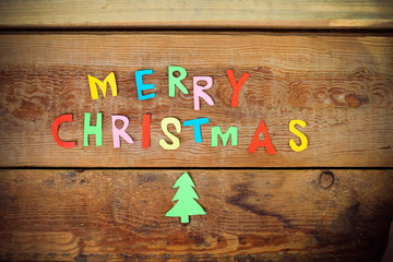 Merry Christmas greeting message on wooden background