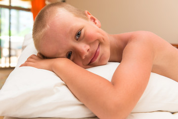 happy smiling little boy lying on a pillow in bed