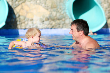 Happy father and daughter playing in swimming pool