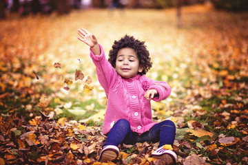 Child playing in park on a beautiful autumn day