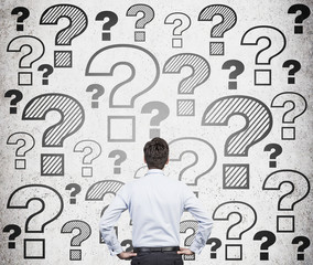 businessman looking at question marks