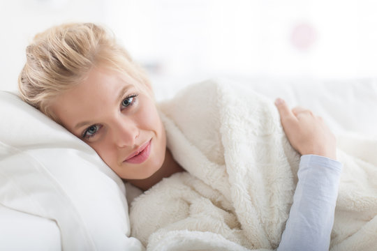 young woman lying on a couch wrapped in a blanket